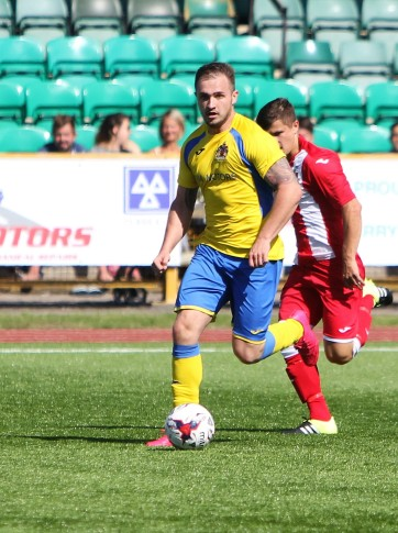 Action as Barry Town (yellow) take on Undy Athletic in the Welsh Football League Division 1.