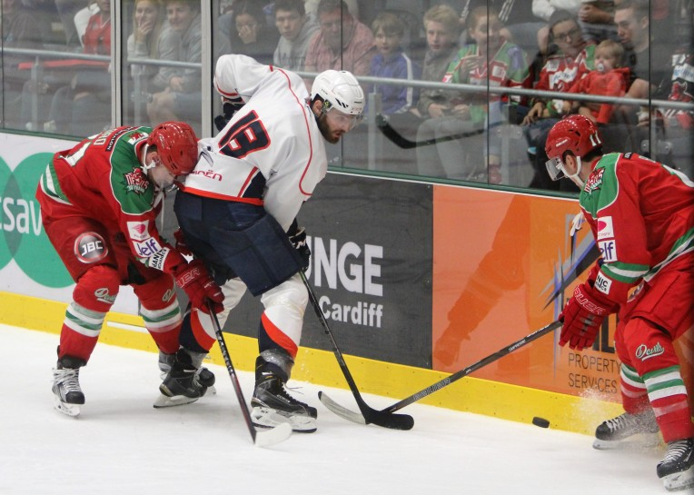 Medvescak's Thomas Larkin (white) battles with Cardiff's Andrew Lord and David Brine.