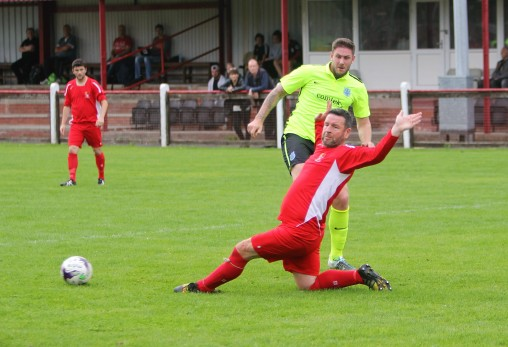 Bedlington's Paul Stoneman (red) gets in a block on Ian Ward's shot for Bishop Auckland.