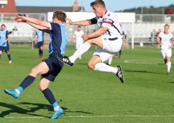 Action as Bishop Auckland (blue) take on Trafford in the FA Cup.