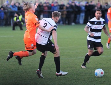 Halifax's Matty Kosylo (orange) leaps into a challenge on Darlington's Terry Galbraith.