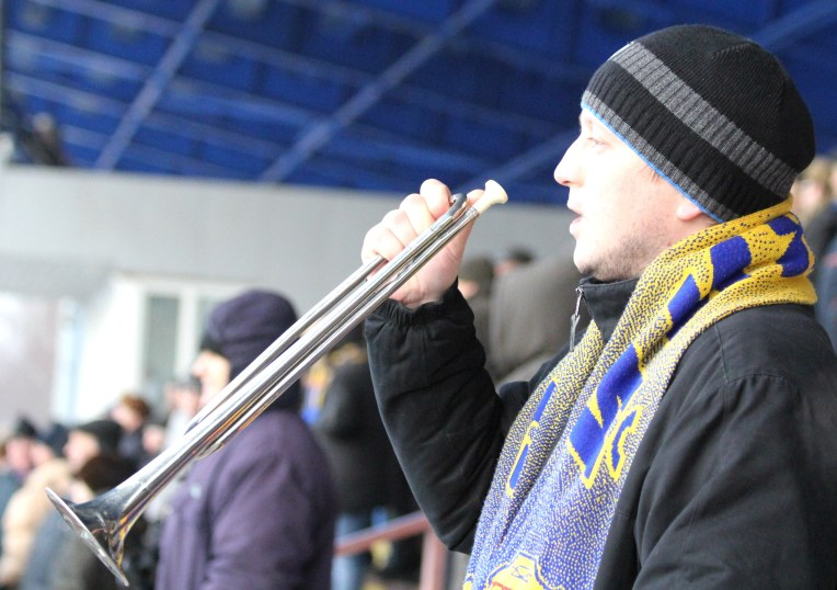 A Zorki Krasnogorsk fan greets his team with a fanfare.