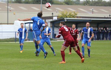 Glossop defender Michael Bowler heads clear under pressure from Spennymoor forward Liam Richardson.