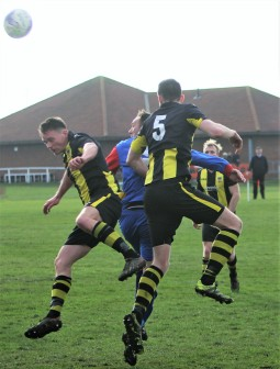 Tow Law's Micky Gibson rises between two Hebburn defenders to loop a header into the net.