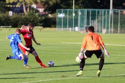 A Knaresborough Town forward (red) fires in a shot against Pickering.