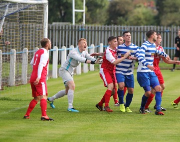 Ashton United (red) defend a corner at Newcastle Benfield.