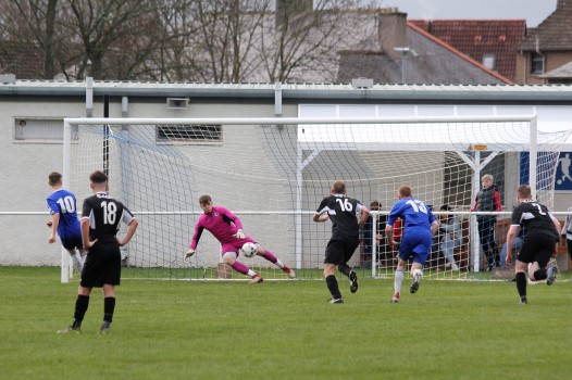 Coldstream (blue) wrap up a 3-1 win over Musselburgh from the penalty spot.