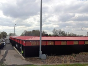 Bright red roofs on the stands at Salford City's ground.